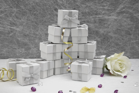 gold table cloth: Wedding Favor boxes on a White tablecloth with gold ribbons, bows, silver heart confetti and small diamond table decorations Stock Photo