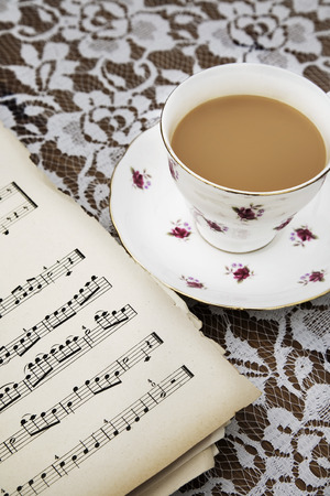 key signature: Vintage tea cup,saucer and Old Musical Score Sheets on a flora tablecloth Stock Photo