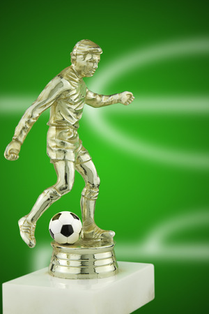 real trophy: close up of a gold plastic football player trophy with a real leather football Stock Photo