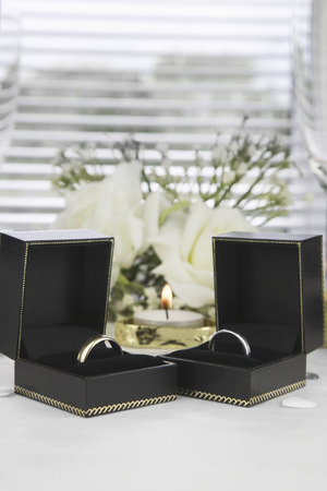 white gold: Bride and Groom Gold and White Gold wedding rings in there boxes with a wedding table setting in the background