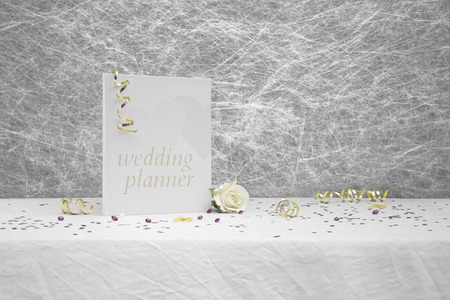 table decorations: Wedding planner book on a White tablecloth with gold ribbons, bows, silver heart confetti and small diamond table decorations
