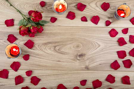 Red fabric rose and rose petals with candle tealights on a wood background