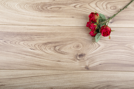 Red fabric rose on a wood background