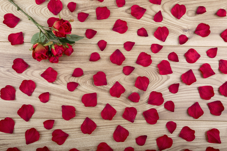 Red fabric rose and rose petals on a wood background Imagens