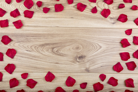 Red fabric rose petals with copy space in the centre on a wood background
