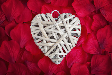 wooden love heart on red fabric rose petals
