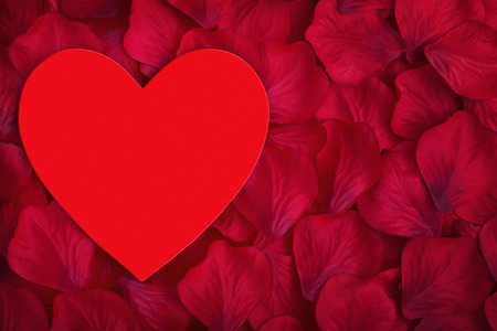 Red love heart with space for copy on red fabric rose petals