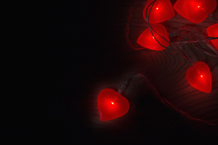 Valentines red love heart lights glowing on a wood background
