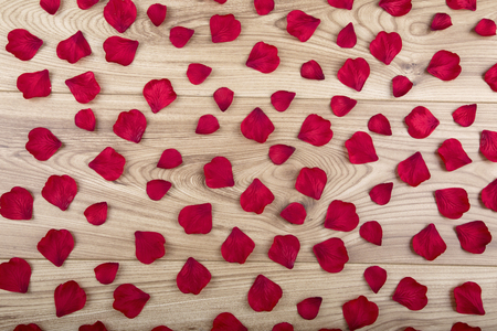 Red fabric rose petals on wooden floorboards