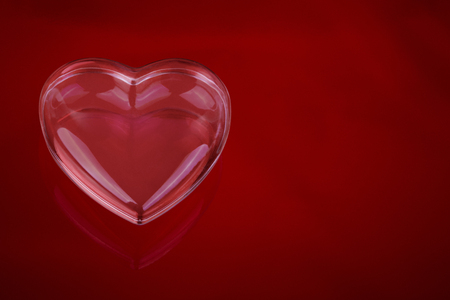 glass love heart on red background Imagens