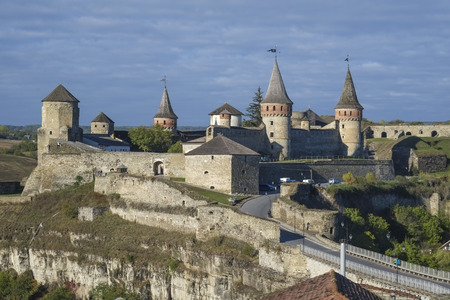 View of the Most Zamkowy and Castle of Kamianets-Podilskyi in Western Ukraine taken on a sunny autumn day. The cobbled street leads the eye across the bridge to the castle