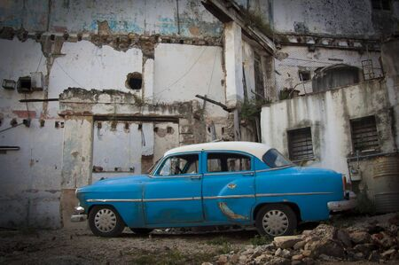 Classic American Car on Derelict Buidling Lot in Havana Cuba with rubble and exposed walls