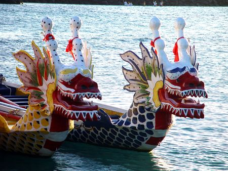 Two dragon boats rest in the sea.