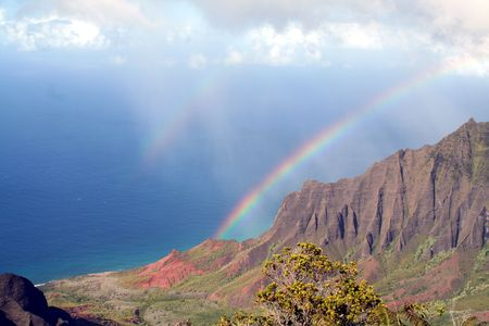 A rainbow stretches from the clouds to the sea.