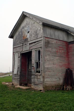 one room school house: An old one room school house in a field on a cloudy day.