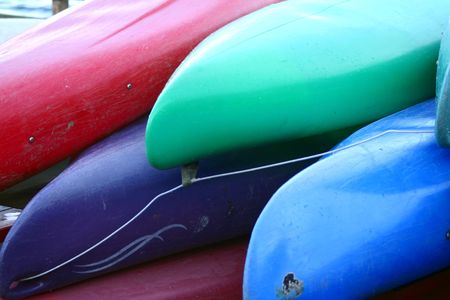 Colorful canoes stacked on one the shore.