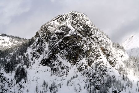 blanketed: Looking at a snow covered mountain with avalanche areas. Stock Photo