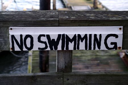 no swimming: An old wood sign painted with No Swimming.
