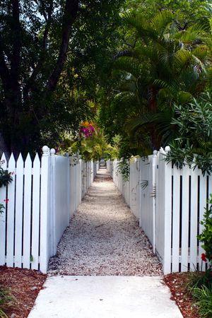Een wandelpad omzoomd door witte picket fences en tropische gebladerte