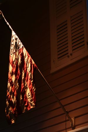 An American flag hangs at night under a light. Stock Photo