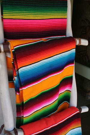 Several colorful Mexican wool blankets hung on display.