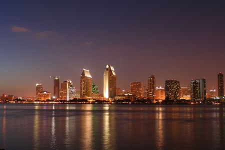 A cityscape in the even with lights reflected in water.
