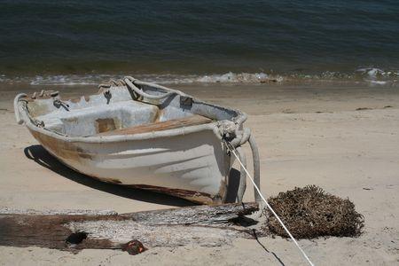 An old row boat on a white sand beach