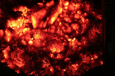 A pile of red hot embers glowing in the darkness.