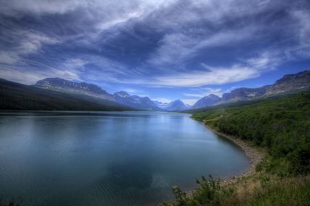 A blue mountain lake with thin white clouds shoot in High Dynamic Range. Imagens