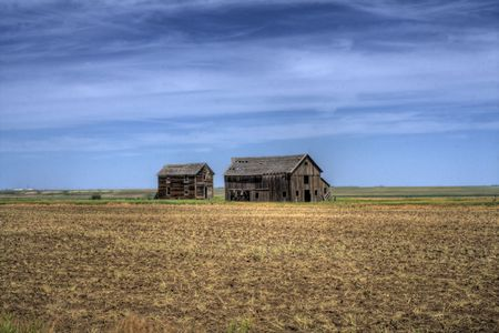 This old homestead is abandoned and sits in the middle of a wide open prairie. Stock Photo - 5452263