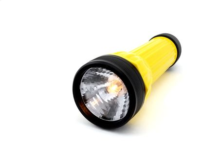 torchlight: A flashlight isolated on white with the bulb turned on.