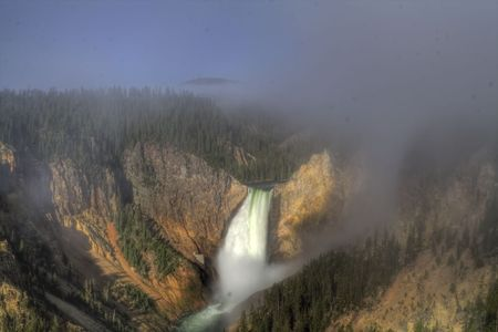 A waterfall flowing into a canyon with clouds and fog. Shot in HDR. photo