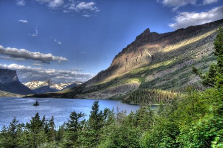 A blue mountain lake with thin white clouds shoot in High Dynamic Range. Stock Photo