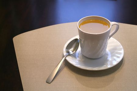 A cup of soup on a dark table with a placemat. Stock Photo - 5571142