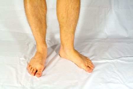 Bare male feet standing on a white cloth.