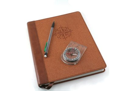 A brown travel journal imprinted with a compass and pencil, isolated on white.