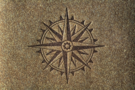 A compass rose imprinted on a wood texture with copy spce. Banco de Imagens