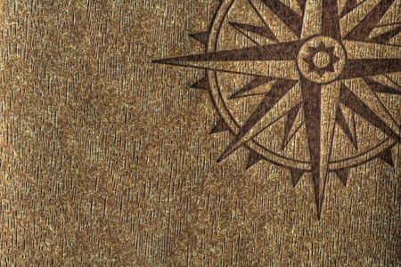 A compass rose imprinted on a wood texture with copy spce. Foto de archivo
