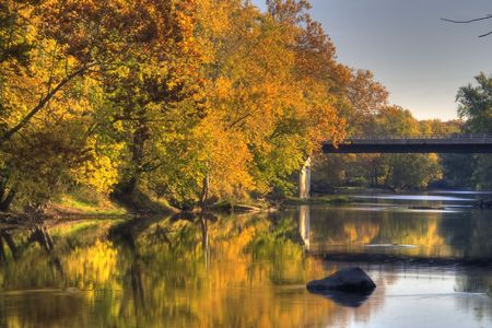 A river flows by fall colored trees Stock Photo