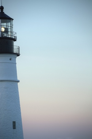 Close up of a light house beacon with the evening sky in the background. Stock Photo