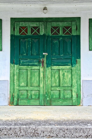 Detail of an old and weathered green door.