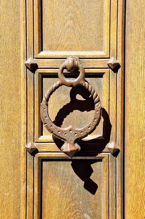 An old door knocker on a wooden door.