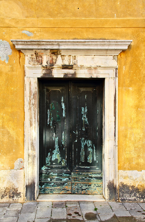 An old green door on a yellow building in Venice, Italy Stock Photo