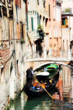 A gondolier piloting his craft on the canals of Venice. Banque d'images