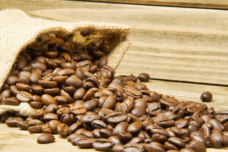 A close up of a burlap bag of coffee beans spilled onto a wood table with the focus on the nearest spilled beans.