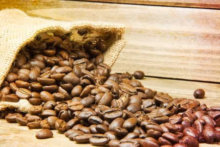 I close up of a burlap bag of coffee beans spilled onto a wood table with the focus centered on the middle of the spilled beans and a texture applied to the edges of the image. Stock fotó
