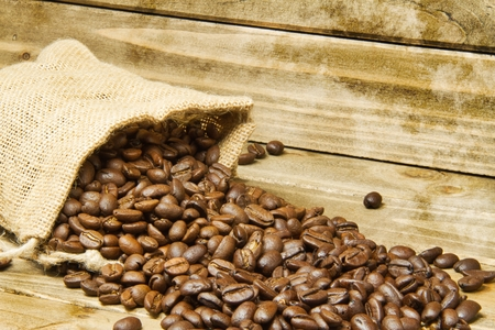 I close up of a burlap bag of coffee beans spilled onto a wood table with a texture applied around the edges of the image.