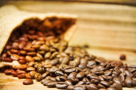 I close up of a burlap bag of coffee beans spilled onto a wood table with the focus on the nearest of the spilled beans and a texture applied to the edges of the image.