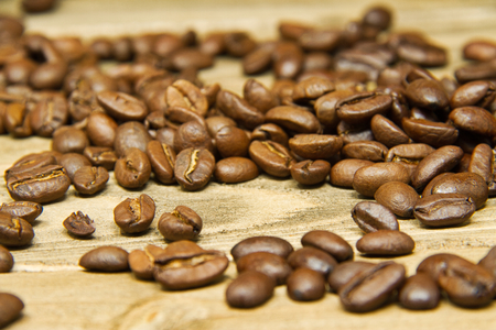 Coffee beans spilled onto a wood table with the focus on the beans in the middle.