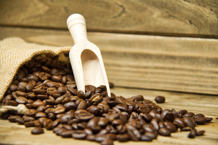 A spilled burlap bag full of coffee beans with a wooden scoop. Imagens